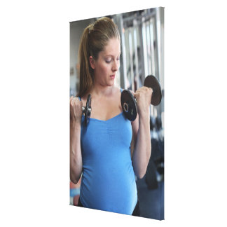 pregnant woman exercising at health club stretched canvas prints