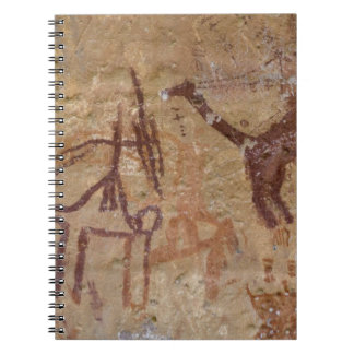 Prehistoric rock paintings with camels and notebook