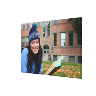 Pretty college student studying in autumn leaves canvas print