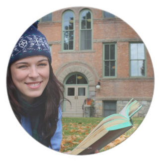 Pretty college student studying in autumn leaves plate