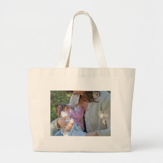 Pretty young brunette mum breastfeeding her baby large tote bag