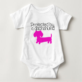 Protected by a Dachshund (pink) Baby Bodysuit