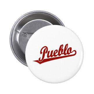 Pueblo script logo in red 6 cm round badge