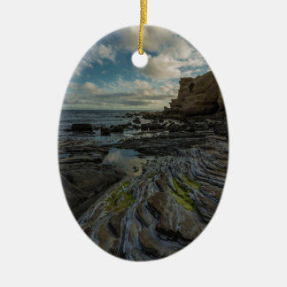 Puffy clouds over rocky shore ceramic oval decoration