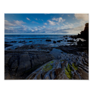 Puffy clouds over rocky shore poster