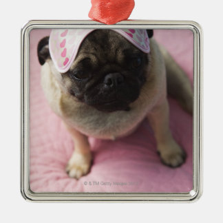 Pug dog with eye mask on head sitting on bed, christmas ornament