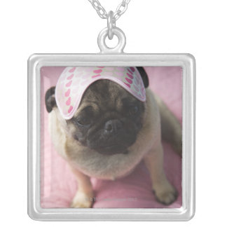 Pug dog with eye mask on head sitting on bed, silver plated necklace