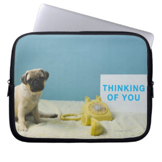 Pug puppy sitting on bed next to phone and laptop sleeve