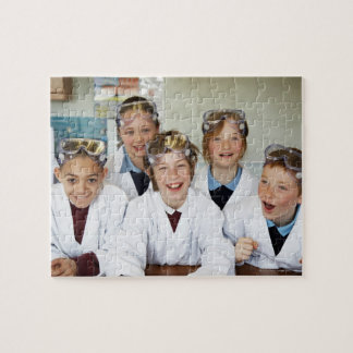 Pupils (9-12) in science class, smiling, jigsaw puzzle