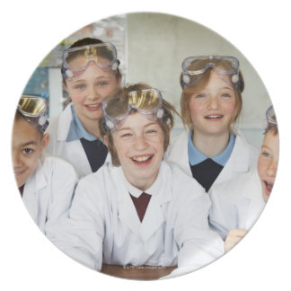Pupils (9-12) in science class, smiling, plate