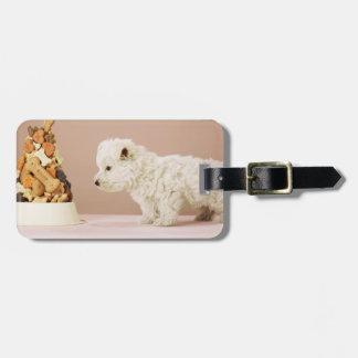 Puppy looking at pile of biscuits in dog bowl luggage tag