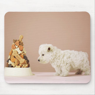 Puppy looking at pile of biscuits in dog bowl mouse mat