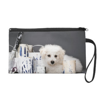 Puppy sitting amongst paint tins wristlet