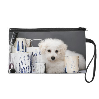 Puppy sitting amongst paint tins wristlet clutches