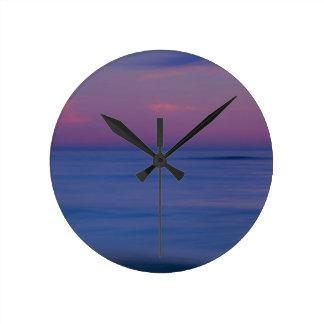 Purple-colored sunrise on ocean shore 2 round clock