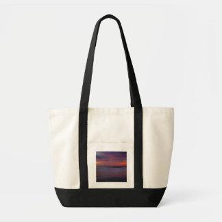 Purple-colored sunrise on ocean shore tote bag