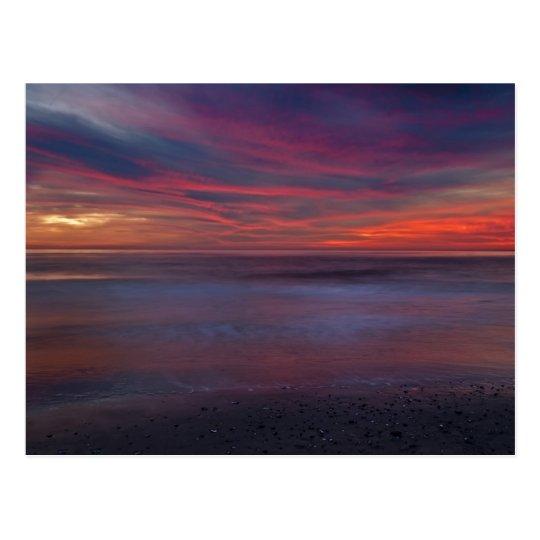 Purple-coloured sunrise on ocean shore postcard