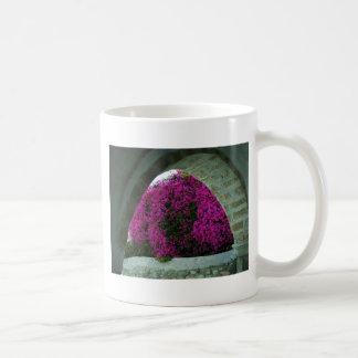 Purple flowers through an arch. coffee mug