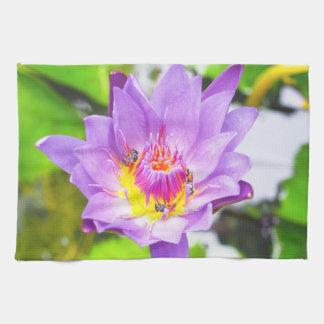 Purple lotus with bees working inside tea towels