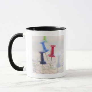 Pushpins in a map mug