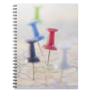 Pushpins in a map notebook