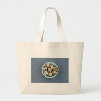 Quails eggs in a green bowl large tote bag