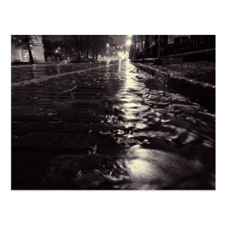 Rain water flowing on a cobblestone street postcard