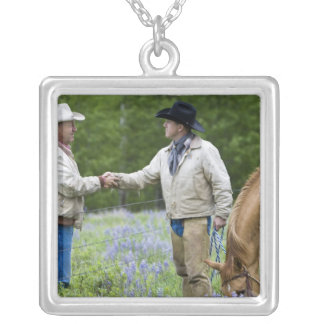 Ranchers shaking hands across the fencing in silver plated necklace