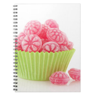 Raspberry tasty candy sweets in green cup cake notebook