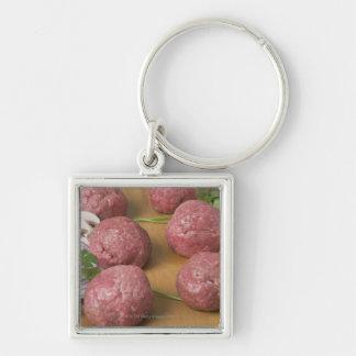 Raw meatballs on a cutting board key ring
