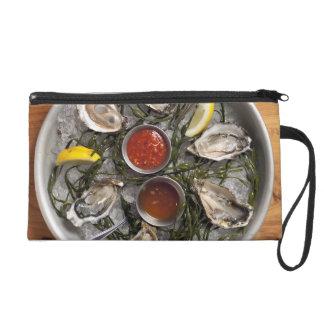 Raw oysters arranged wristlet clutch