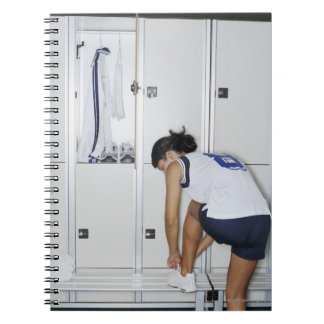 Rear View of a Female Volleyball Player Tying Notebooks
