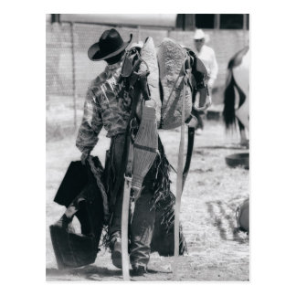 Rear view of cowboy hauling gear postcard