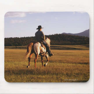 Rear view of cowboy riding horse mouse mat