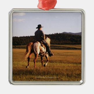 Rear view of cowboy riding horse Silver-Colored square decoration