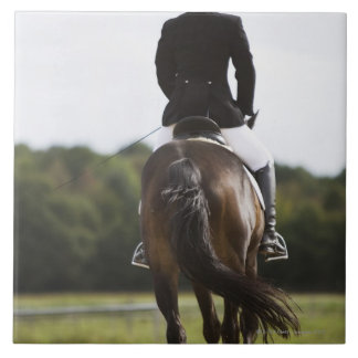 rear view of female dressage rider exercising tile