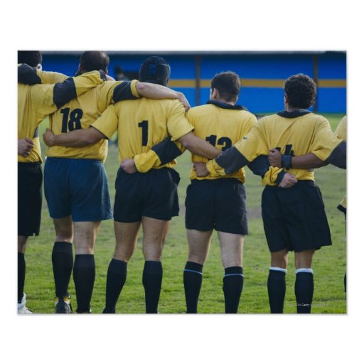 Rear view of rugby team standing with their arms poster