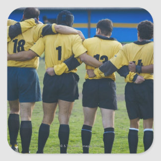 Rear view of rugby team standing with their arms square sticker