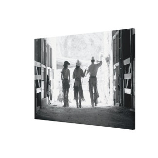 Rear view of three ranch hands leaving stable canvas print
