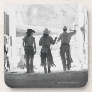 Rear view of three ranch hands leaving stable coaster