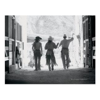 Rear view of three ranch hands leaving stable postcard