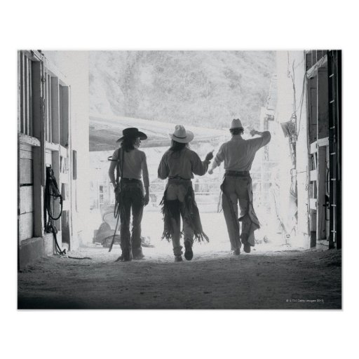 Rear view of three ranch hands leaving stable posters