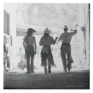 Rear view of three ranch hands leaving stable tile