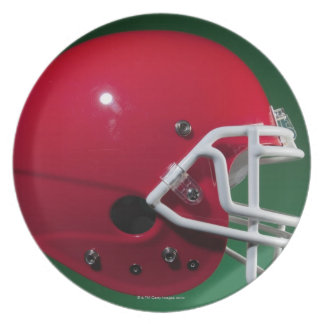 Red American football helmet on green background Dinner Plates