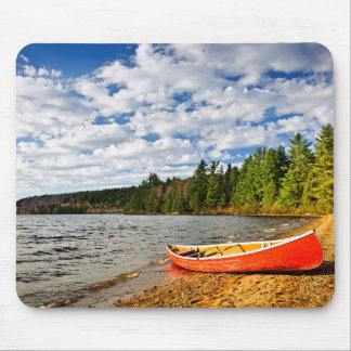 Red canoe on lake shore mouse pad