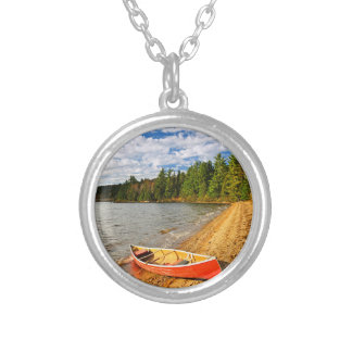 Red canoe on lake shore round pendant necklace