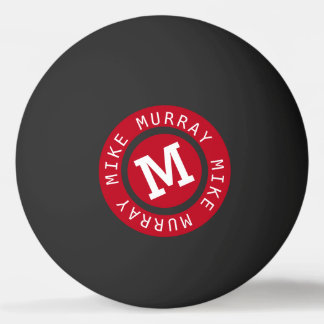 red circle monogram on black ping pong ball