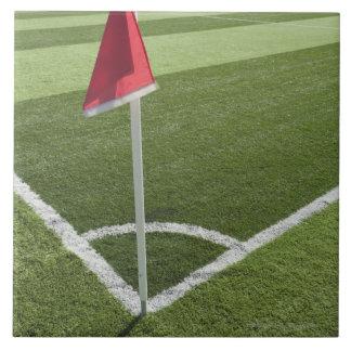 Red corner flag on soccer field large square tile