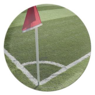Red corner flag on soccer field plate