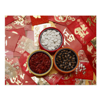 Red envelopes with melon seeds scattered on table postcard